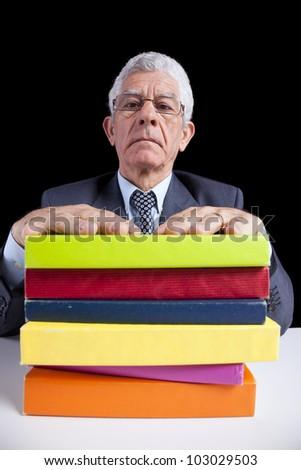 Senior teacher portrait behind some books (isolated on black) - stock photo