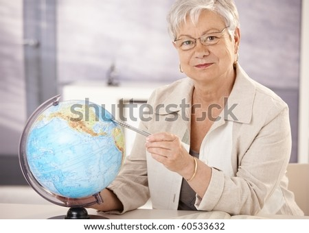 Senior teacher sitting at desk, pointing at globe, teaching geography in elementary school.? - stock photo
