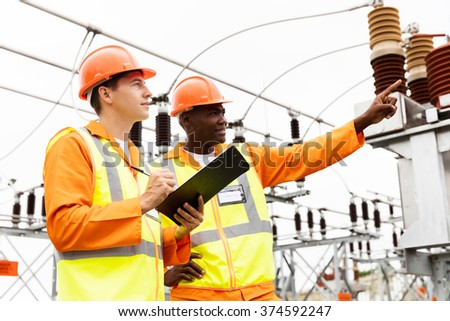 senior technician and electrician working together in power plant - stock photo