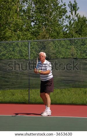 Senior Tennis Player, Preparing to Serve - stock photo