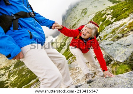 Senior tourist couple hiking, man is helping woman to get to the rock - stock photo