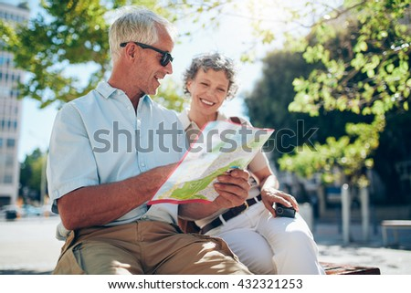 Senior tourist sitting on a bench and looking for a place on the map. Relaxed mature couple on a holiday, using a map for finding their destination. - stock photo