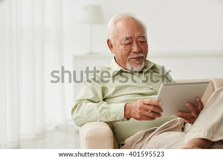 Senior Vietnamese man sitting on sofa and reading new on his tablet computer - stock photo