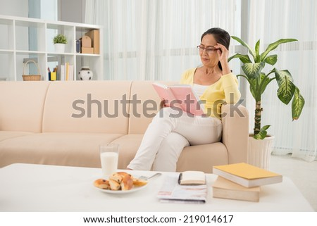 Senior Vietnamese woman in glasses reading a book - stock photo