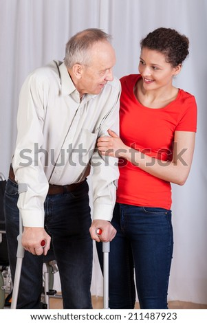 Senior walking with crutches insured by physiotherapist - stock photo