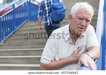 Senior weak man is walking down stairs - stock photo