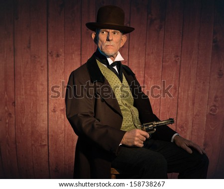 Senior western man wearing a brown hat and coat holding a revolver gun. Sitting on chair in front of wooden wall in saloon. - stock photo