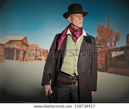 Senior western man wearing a brown hat and coat holding a revolver gun. Standing in old small cowboy town. - stock photo