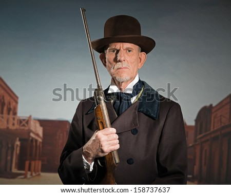 Senior western man wearing a brown hat and coat holding rifle. Standing in old small cowboy town. - stock photo