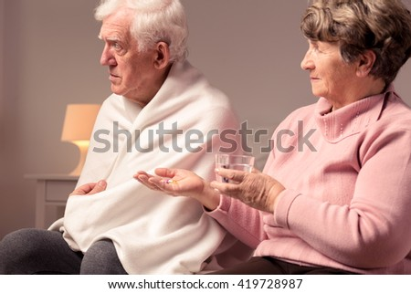 Senior wife giving medicines to her sick husband - stock photo