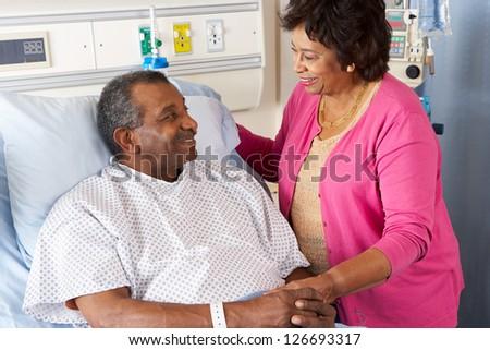 Senior Wife Visiting Husband On Ward - stock photo