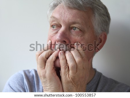 senior with an anxious, fearful expression - stock photo