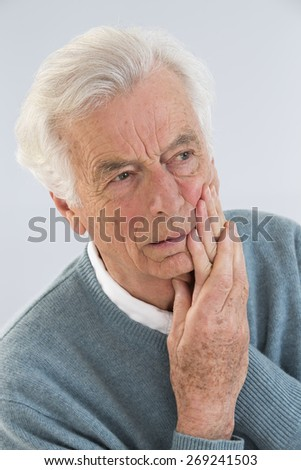 senior with cheek soreness or tooth pain - stock photo