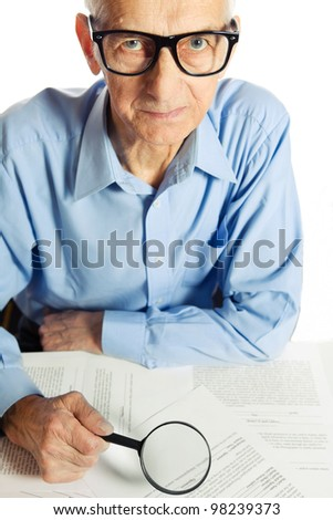 Senior with magnyfiying glass is looking at  documentation through magnifying glass. - stock photo