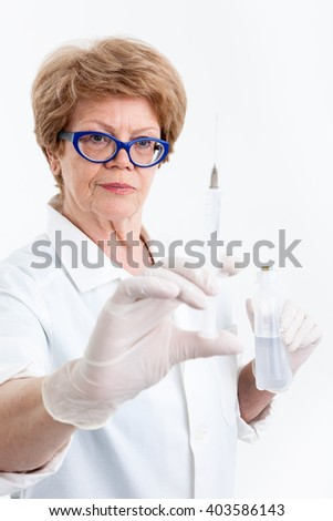 Senior woman a nurse looking at syringe for vaccination in her hand, focus on face, white background - stock photo