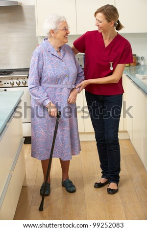 Senior woman and carer in kitchen - stock photo