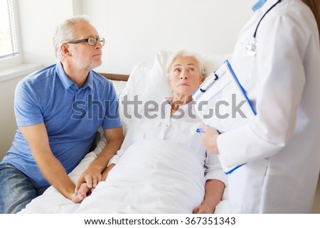 senior woman and doctor with clipboard at hospital - stock photo