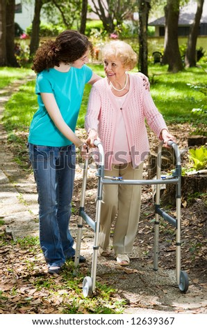 Senior woman and her teen granddaughter taking a walk in the park. - stock photo
