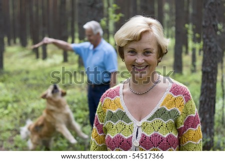 Senior woman and man have fun with a dog in a forest - stock photo