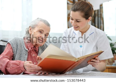 Senior woman and nurse looking together at album with old photographs - stock photo