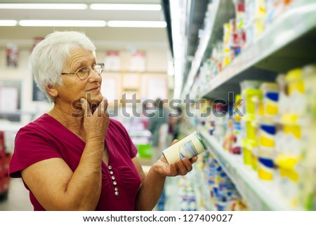 Senior woman at groceries store - stock photo