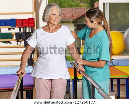 Senior woman at kinesiotherapy with physiotherapist in nursing home - stock photo