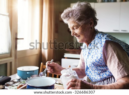 Senior woman baking pies in her home kitchen.  Measuring ingredients.  - stock photo
