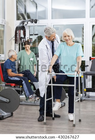 Senior Woman Being Assisted By Doctor At Rehab Center - stock photo