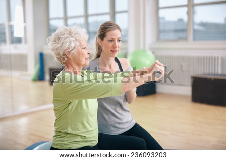 Senior woman being assisted by instructor in lifting dumbbells at gym. Senior woman training in the gym with a personal trainer at rehab. - stock photo