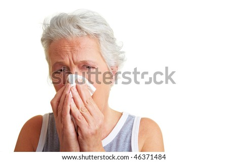 Senior woman blowing her nose with an handkerchief - stock photo