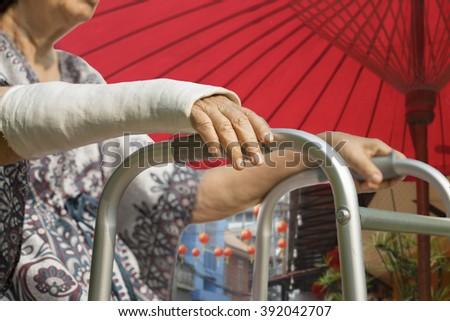 senior woman broken wrist using walker in chinatown - stock photo