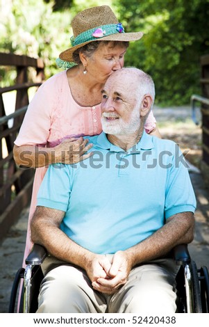 Senior woman caring for her disabled husband. - stock photo