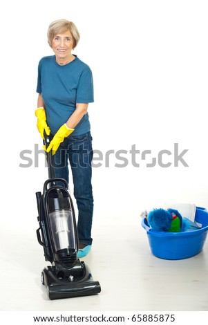 Senior woman cleaning wooden floor  with vacuum cleaner  and smiling - stock photo