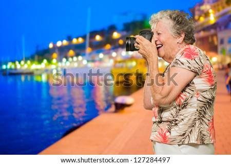 Senior Woman Clicking Photo, Outdoors - stock photo