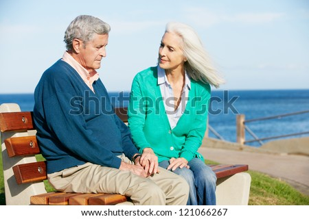 Senior Woman Comforting Depressed Husband Sitting On Bench - stock photo