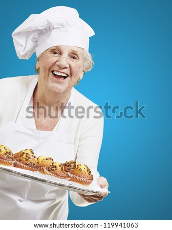senior woman cook holding a tray with muffins against a blue background - stock photo