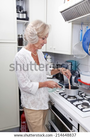Senior woman cooking at kitchen counter - stock photo