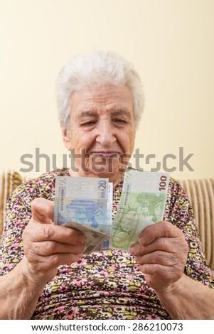 senior woman counting euros - stock photo