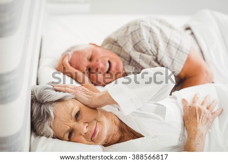 Senior woman covering her ears while man snoring in bed - stock photo