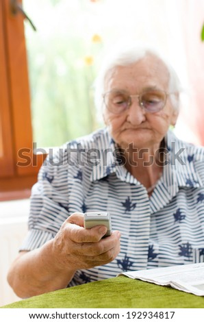 Senior woman dialling number on mobile phone  - stock photo