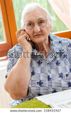 Senior Woman Dialling Number On Mobile Phone Sitting In Chair - stock photo