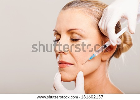 senior woman doing face lifting on her cheek - stock photo