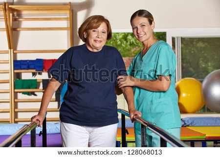 Senior woman doing kinesiotherapy in rehab with physiotherapist - stock photo