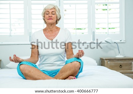 Senior woman doing yoga against window on bed at home - stock photo