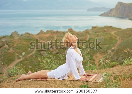 Senior woman doing yoga exercises with beautiful mountain view on the background - stock photo