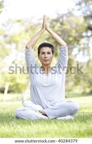 Senior Woman Doing Yoga In Park - stock photo