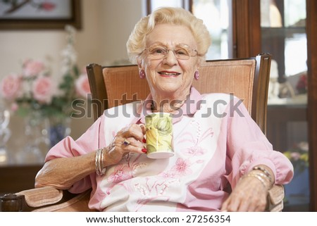 Senior woman drinking hot beverage - stock photo