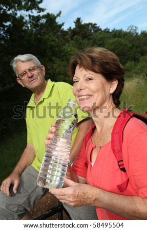 Senior woman drinking water during bike ride - stock photo