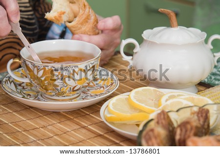 senior woman drinks tea with sweet rolls - stock photo