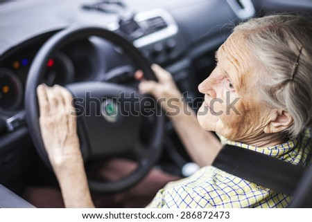 Senior woman driving a car - stock photo
